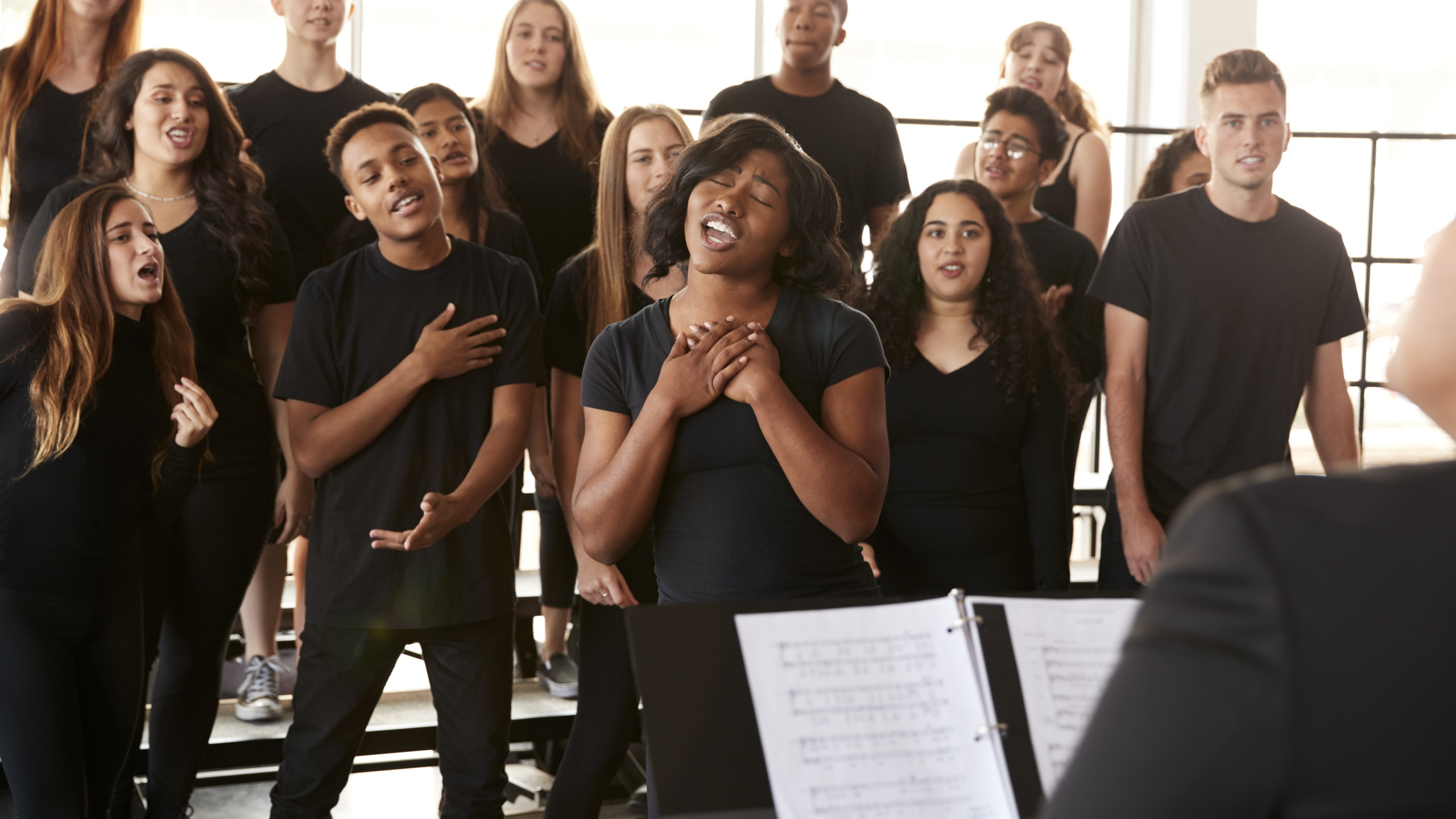 Male And Female Students Singing In Choir With Teacher At Performing Arts School_1557952393796