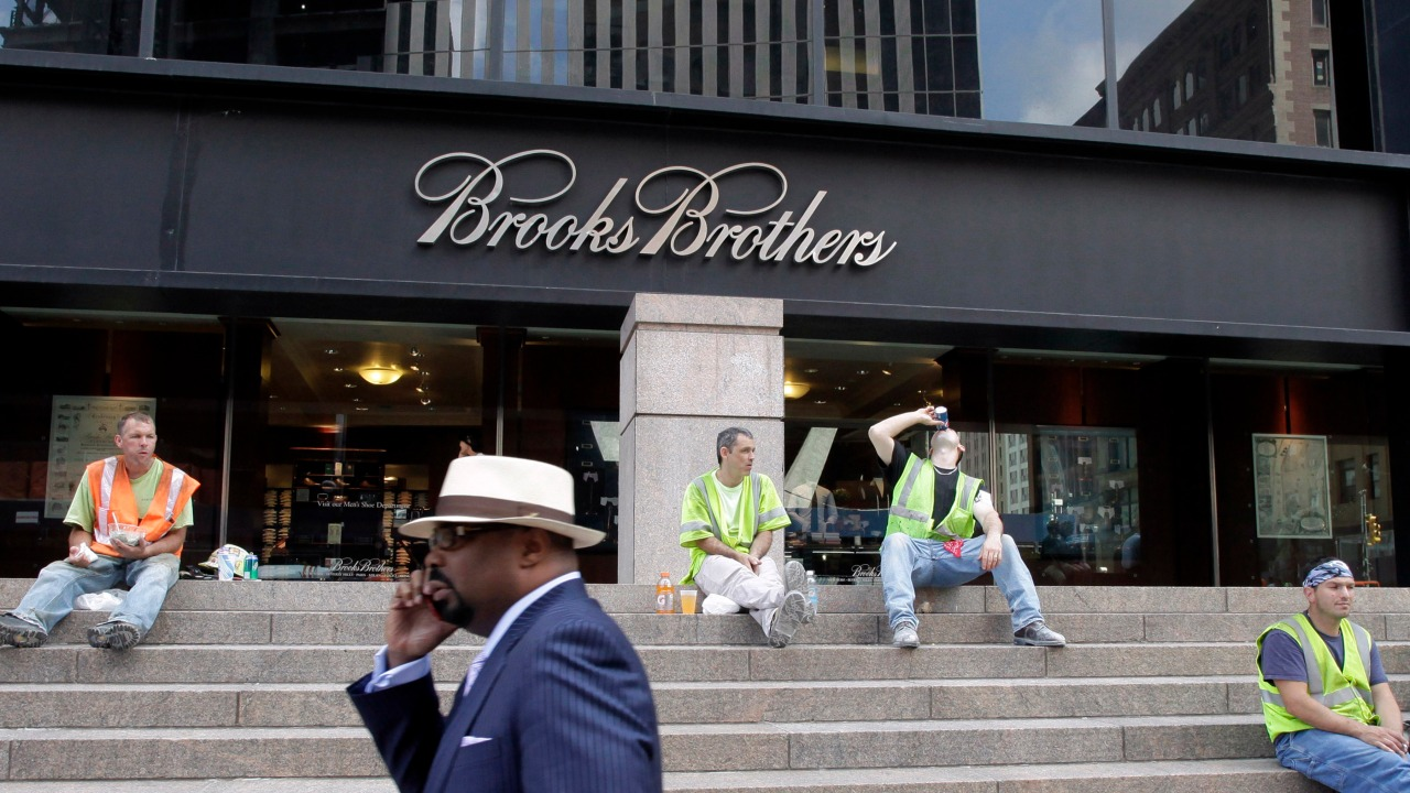 FILE – This is a Sept. 11, 2001, file photo shows a man passing a Brooks Brothers store on Church St. in New York. The storied Manhattan fashion ret